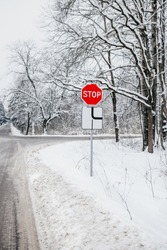 STOP road sign at the crossroads with a main road - road safety in winter