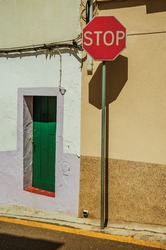 STOP road sign in front colorful house with wooden door on sunny day in Campo Maior. A little town with Moorish and medieval influences in Portugal.