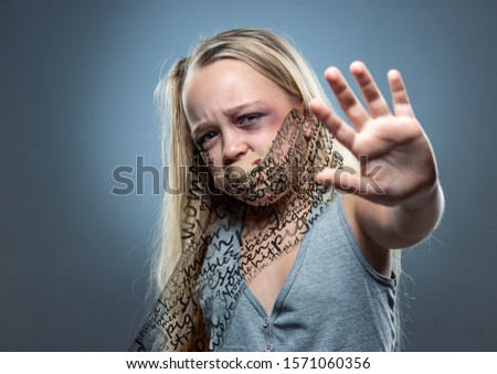 Stop. Sad little girl with bloodshot, bruised eyes and covered mouth. Concept of child violence, domestic abuse. Depressed being victim of parents. Illusion of childhood. Invisible male hand. Design. #1571060356