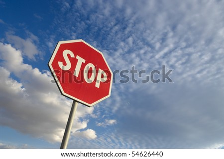 stop sign against blue sky and white clouds