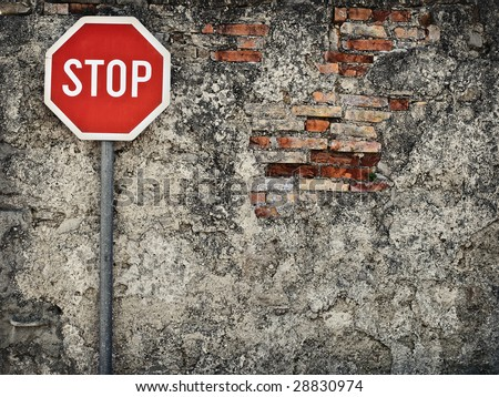 stop sign against grungy wall, may represent protection,dead end...