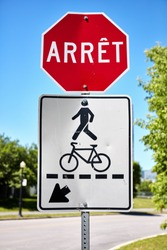 Stop sign (arret) in French and a pedestrian and bicycle sign near a road in Montreal, Canada