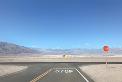 Stop sign by the empty lonely road at the fork in the road and Death Valley National park, California landscape on the background. Stop sign by the empty  road