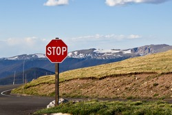 Stop sign on mountain with blue sky background