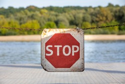 Stop sign on suspended chain. Road sign to warn to stop. Background with nature and vegetation.