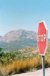 stop sign on the road in the mountains in spain during a road trip in summer holiday