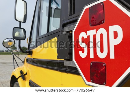 Stop sign on yellow school bus and the reflection in the mirror