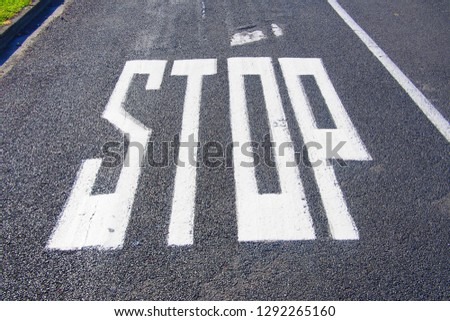 Stop sign painted on asphalt road #1292265160