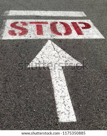 STOP sign with red lettering on white background on street asphalt.  #1175350885