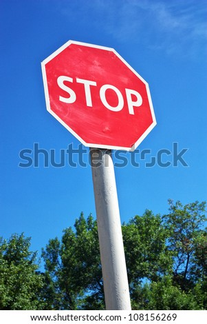 Stop sign, with trees and sky