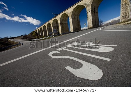 Stop Signal in a Crossroad . Foreground of a Stop Signal Painted on Ground at a Crossroad with a Bridge at Bottom