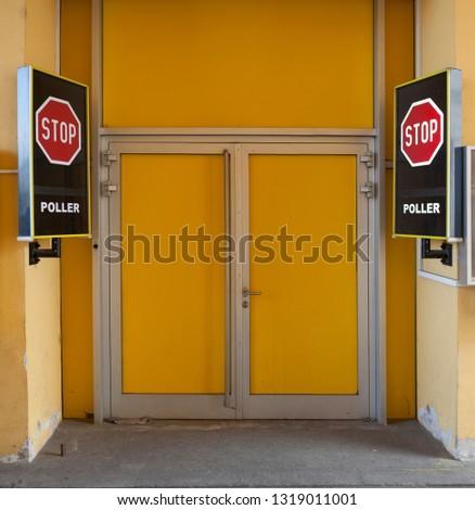 Stop signboards next to the closed yellow door  #1319011001