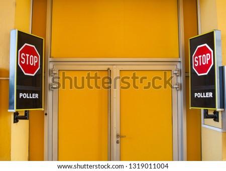 Stop signboards next to the closed yellow door  #1319011004