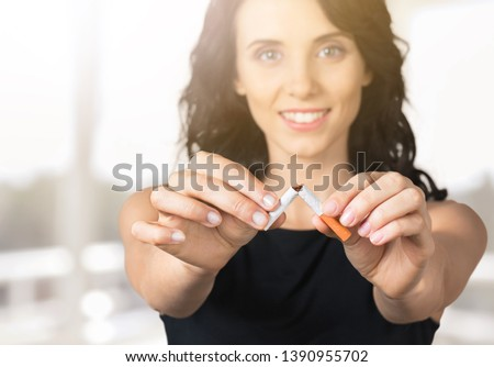 Stop smoking cigarettes concept. Close up of young smiling girl holds broken cigarette in hands. Happy female quitting smoking cigarettes. Quit bad habit, health care concept. No smoking. Tonned