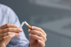 Stop smoking concept. Close-up of man quitting with smoking habit and breaking cigarette on half.