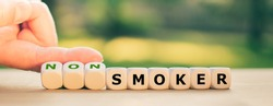 Stop smoking concept. Hand turns dice and changes the word