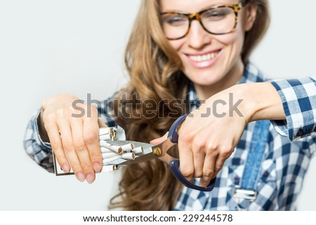 Stop smoking concept. Young woman cut cigarettes with scissors happy smiling. focus on hand, scissors and cigarettes