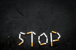 Stop smoking. Word stop lined cigarettes on black background top view copy space
