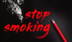 Stop smoking words, red pencil and smoke on black background. No smoking quit addiction concept.