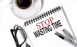 stop wasting time. text on white notepad paper on white background.