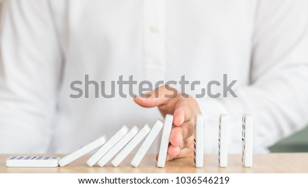 Stopping domino effect concept for business solution strategy, financial or investment protection and successful intervention with corporate person's hand blocking the collapse disruption
