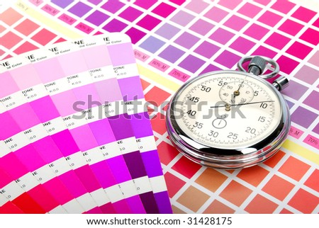 Stopwatch and a color guide on printed color chart (purple pink and red)