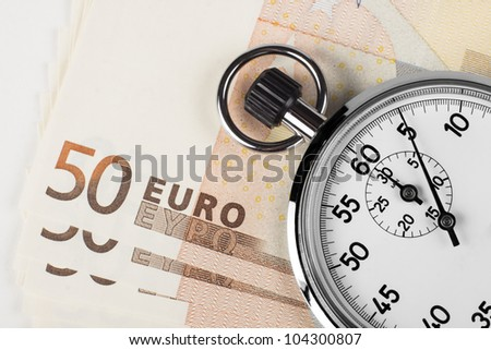 stopwatch closeup pointing at 5 seconds on a pile of 50 euro bills isolated on white background