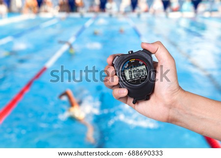 Stopwatch holding on hand with competitions of swimming background. #688690333