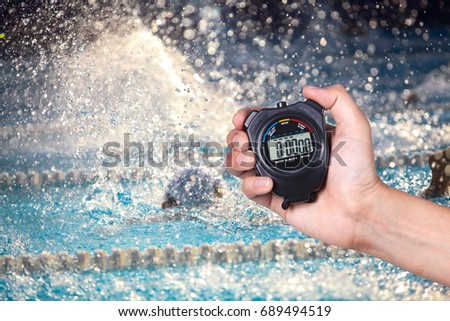 Stopwatch holding on hand with competitions of swimming background. #689494519