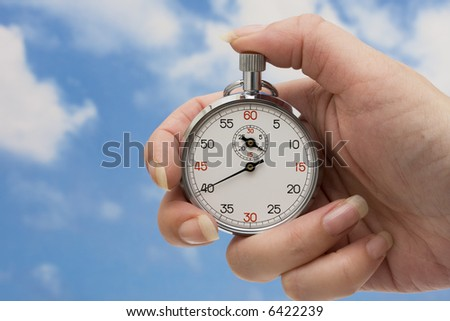 Stopwatch in hand with a sky background - stock photo