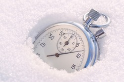 Stopwatch in the snow. Concept of the beginning or end of winter.