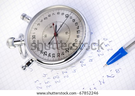Stopwatch on paper with results and pen
