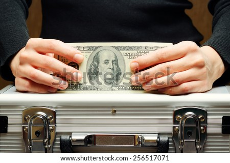 Storage and protection of cash and valuable items. Banking concept. Aluminum briefcase and a hundred-dollar bill. Money and documents in safe hands of bank employee.