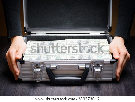 Storage and protection of cash and valuable items. Banking concept. Business man opens an aluminum briefcase full of stacks of hundred dollar bills. Money in safe hands.