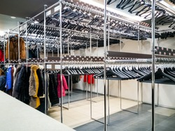 Storage of outerwear in the wardrobe in public place. Hangers in row Cloakroom in Public building locker for clothing- filled frame wallpaper background, horizontal rows of hung .winter clothes.