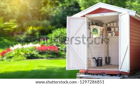 Photo of  Storage shed filled with gardening tools. Beautiful green botanical garden in the background. Copy space for text and product display.
