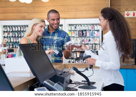 Store assistant handing over the card to a couple after completion of payment for the purchase Сток-фото ©