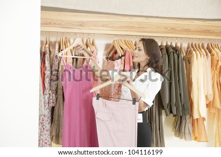 Store assistant sorting clothes on store's rails, smiling.