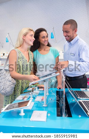 Store manager assisting two customers in a computer store Сток-фото ©