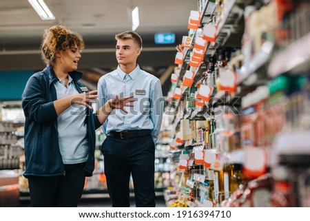 Store manager training young worker. Supermarket manager giving training to a trainee.
