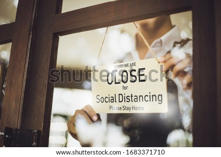 Store owner turning close sign broad through the door glass for social distancing prevent corona virus outbreak. Foto stock ©