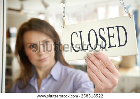 Store Owner Turning Closed Sign In Shop Doorway #258518522