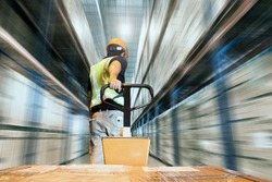 Storehouse area, Shipment. Speeding motion of warehouse worker unloading pallet goods in warehouse storage, his using with hand pallet truck.