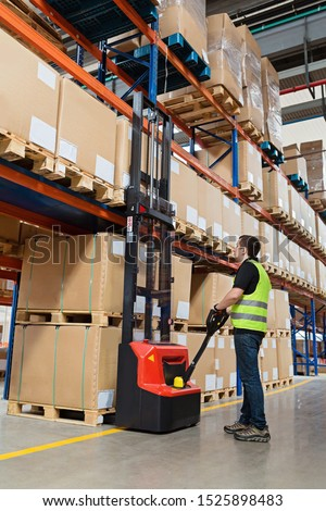 Storehouse employee in uniform working on forklift in modern automatic warehouse.Boxes are on the shelves of the warehouse. Warehousing, machinery concept. Logistics in stock.