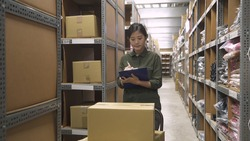 storehouse female worker writing on clipboard and inspecting shipment products for load into truck while standing in stockroom