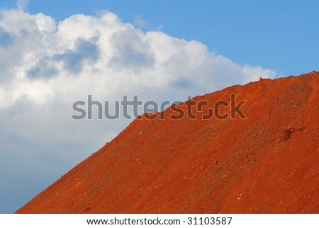 Storehouse, red color of  oxidized iron ores on  background of  sky with clouds