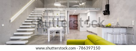 Storied loft apartment with green couch, stairs, table and open kitchen, panorama