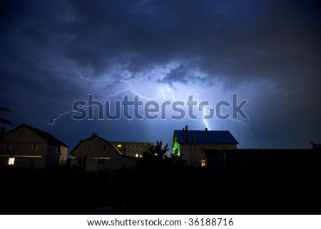Storm and lighting over house. Thunderstorm at night near village.