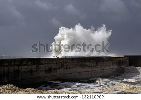 Storm at the harbor of the mouth of the river Douro, in Porto, Portugal, with big waves against pier; close-up