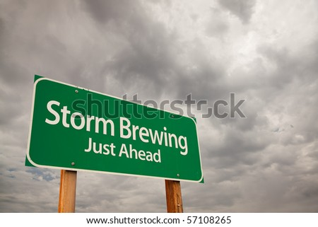 Storm Brewing Just Ahead Green Road Sign with Dramatic Storm Clouds and Sky.